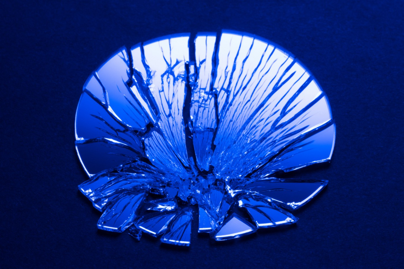 A blue-tinted photo of a shattered mirror.
