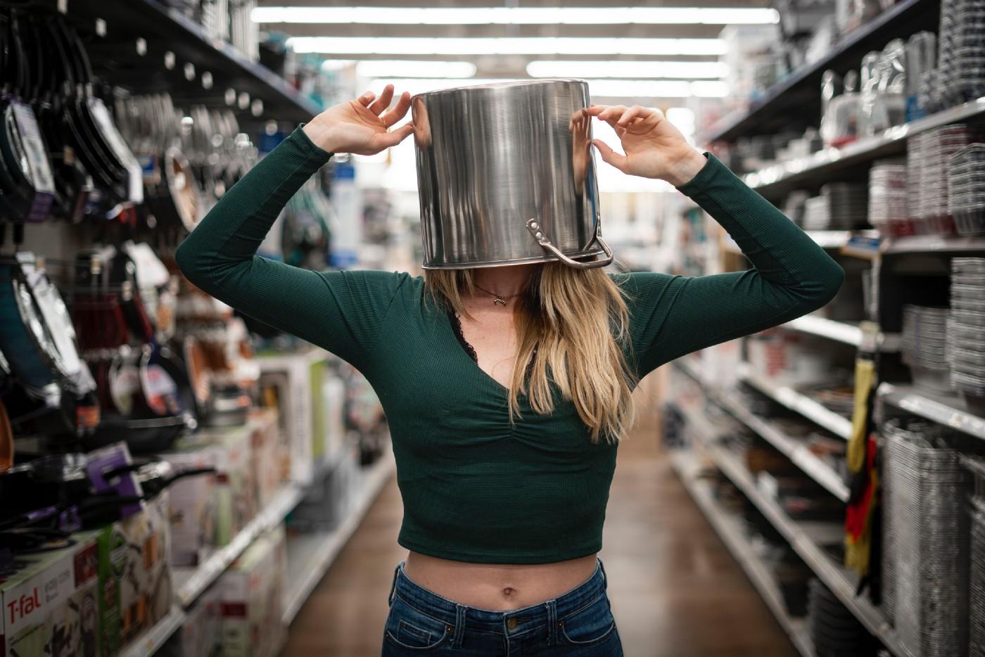 Woman standing in supermarket aisle with a pot on her head