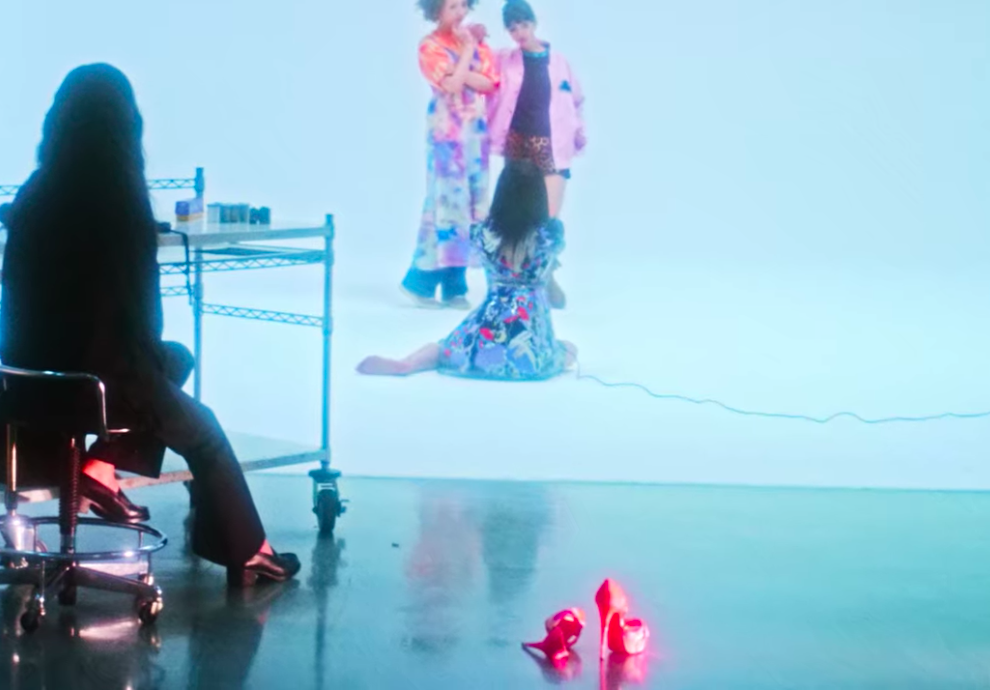 """Limi, the main character of """"Followers,"""" is sitting barefooted while taking photos of the two models in a studio, while her high heels are lying behind her."""
