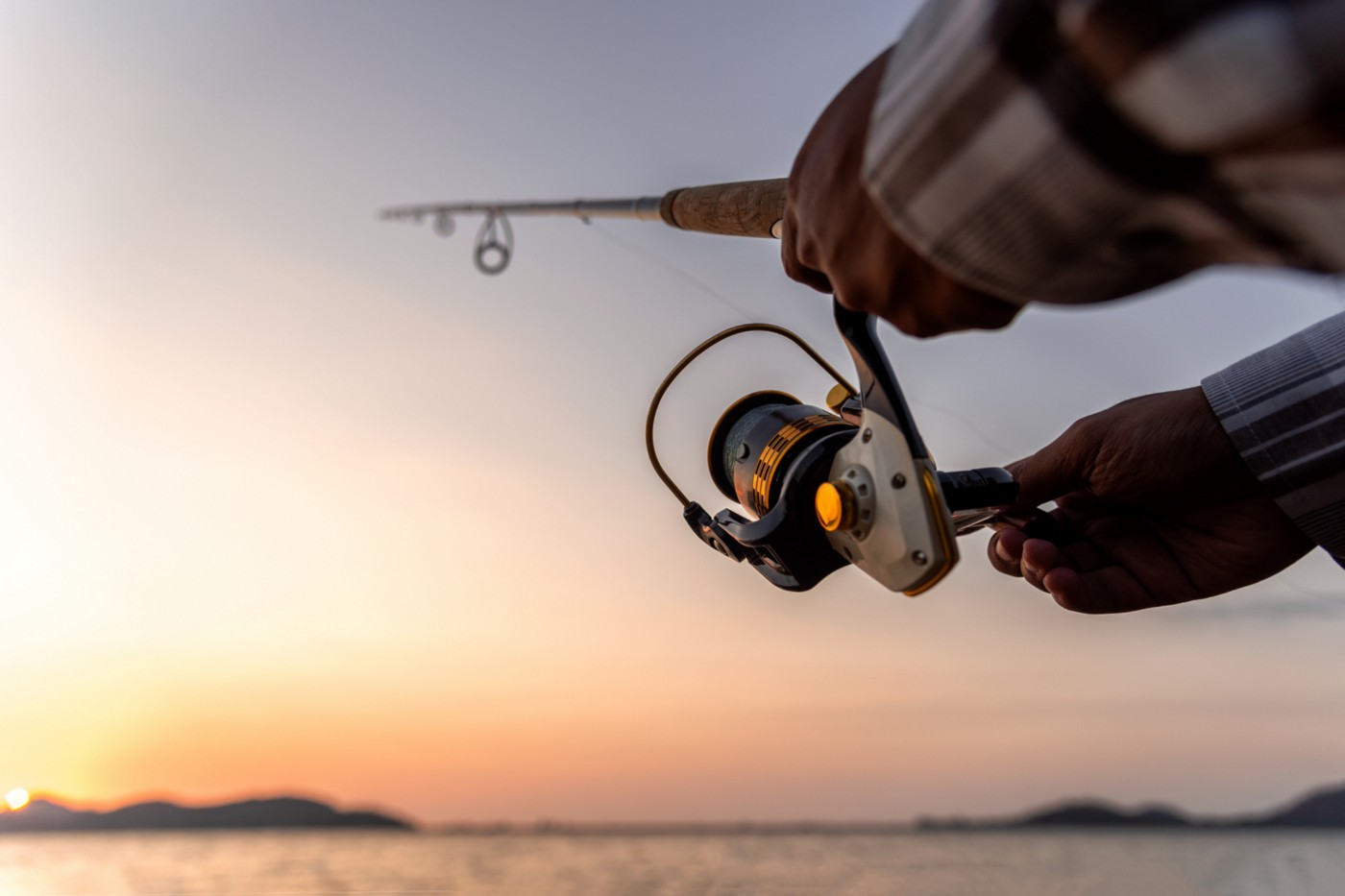 Hands holding a fishing rod and reel.