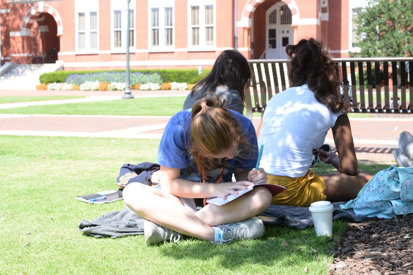 Female student on Samford Lawn writing in her notebook.