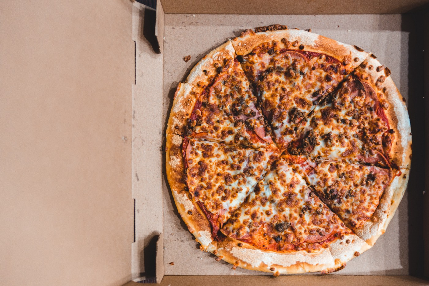 Overhead view of a pizza in an open cardboard delivery box.