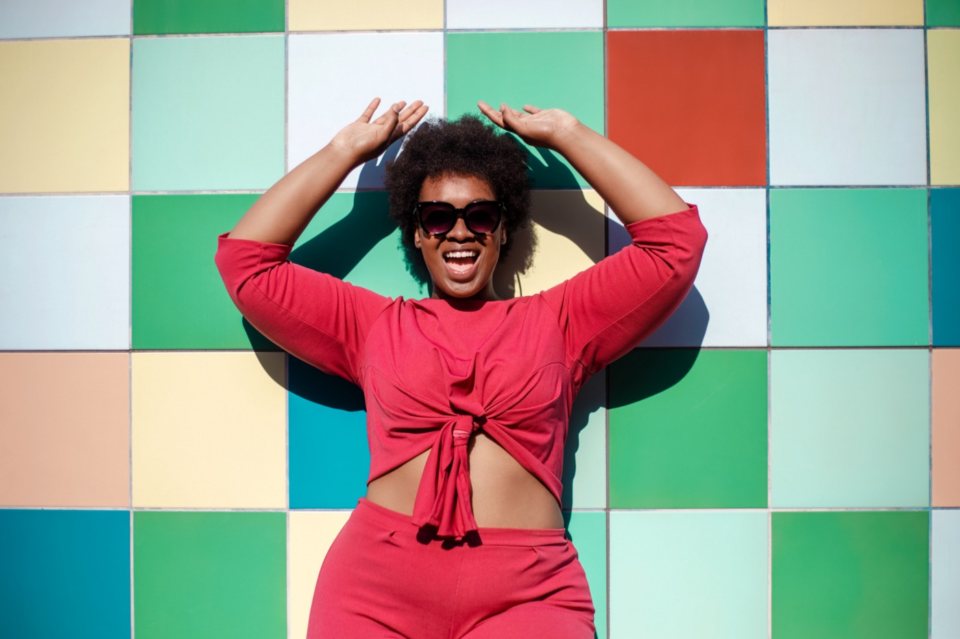 Stylish Black woman in sunglasses and red outfit posing in front of a colorful tiled wall.