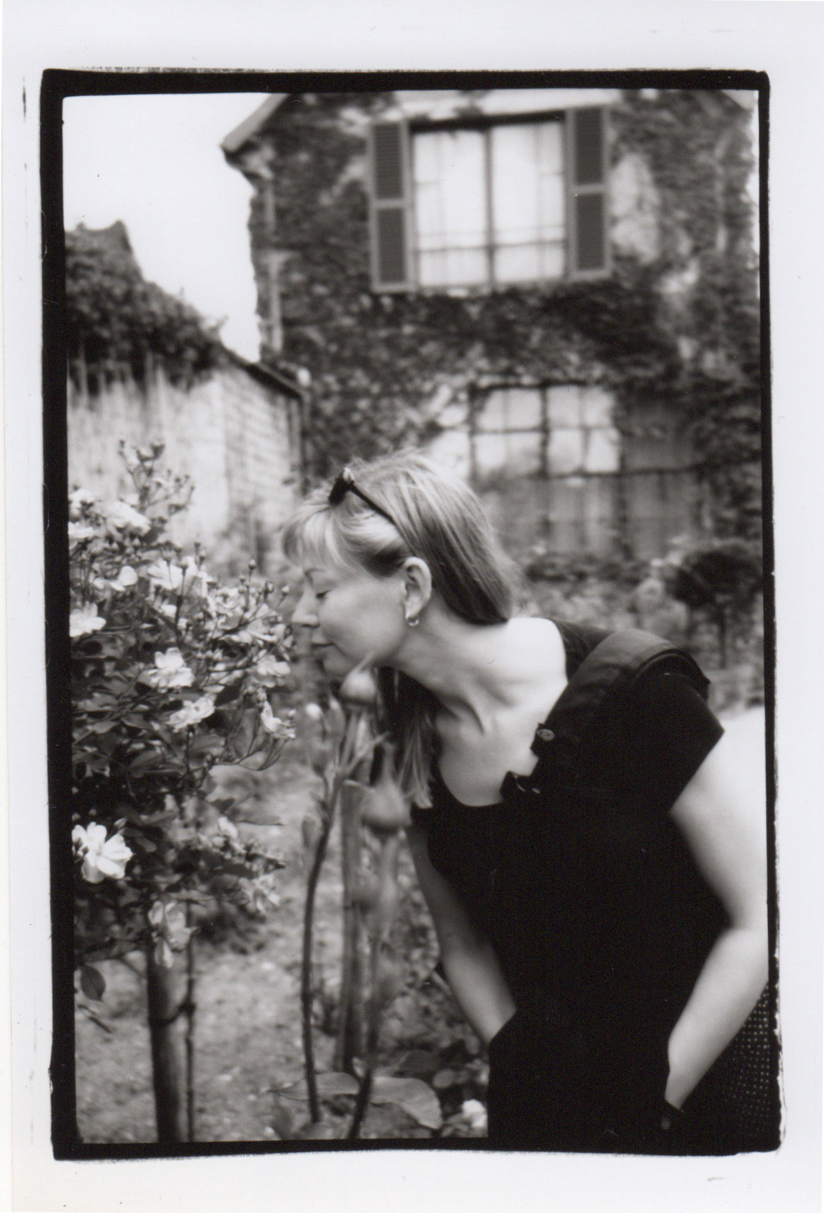 The author, Julie Lindow, smelling a rose in Claude Monet's garden.