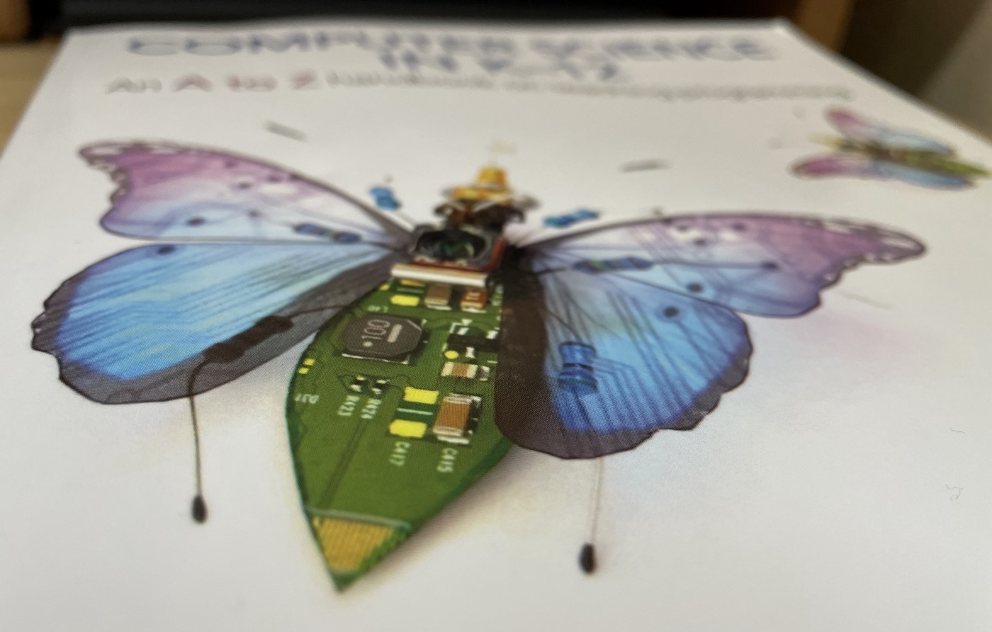 A photograph of the book over showing a robotic butterfly and the book title, blurred in the background.