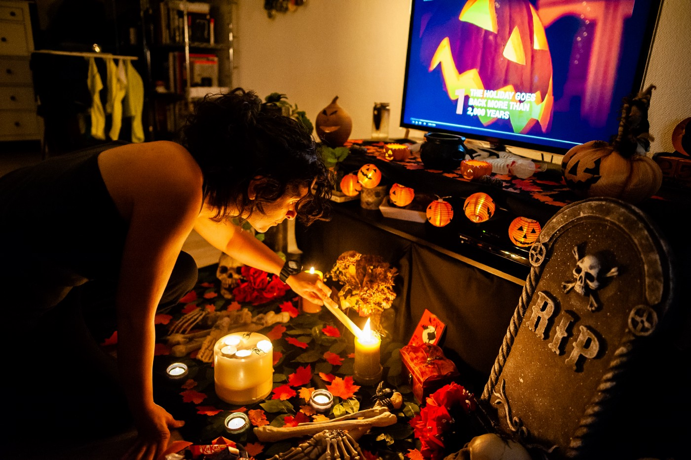 A person lights a candle on an altar on the floor in front of a TV displaying a jack-o'-lantern.