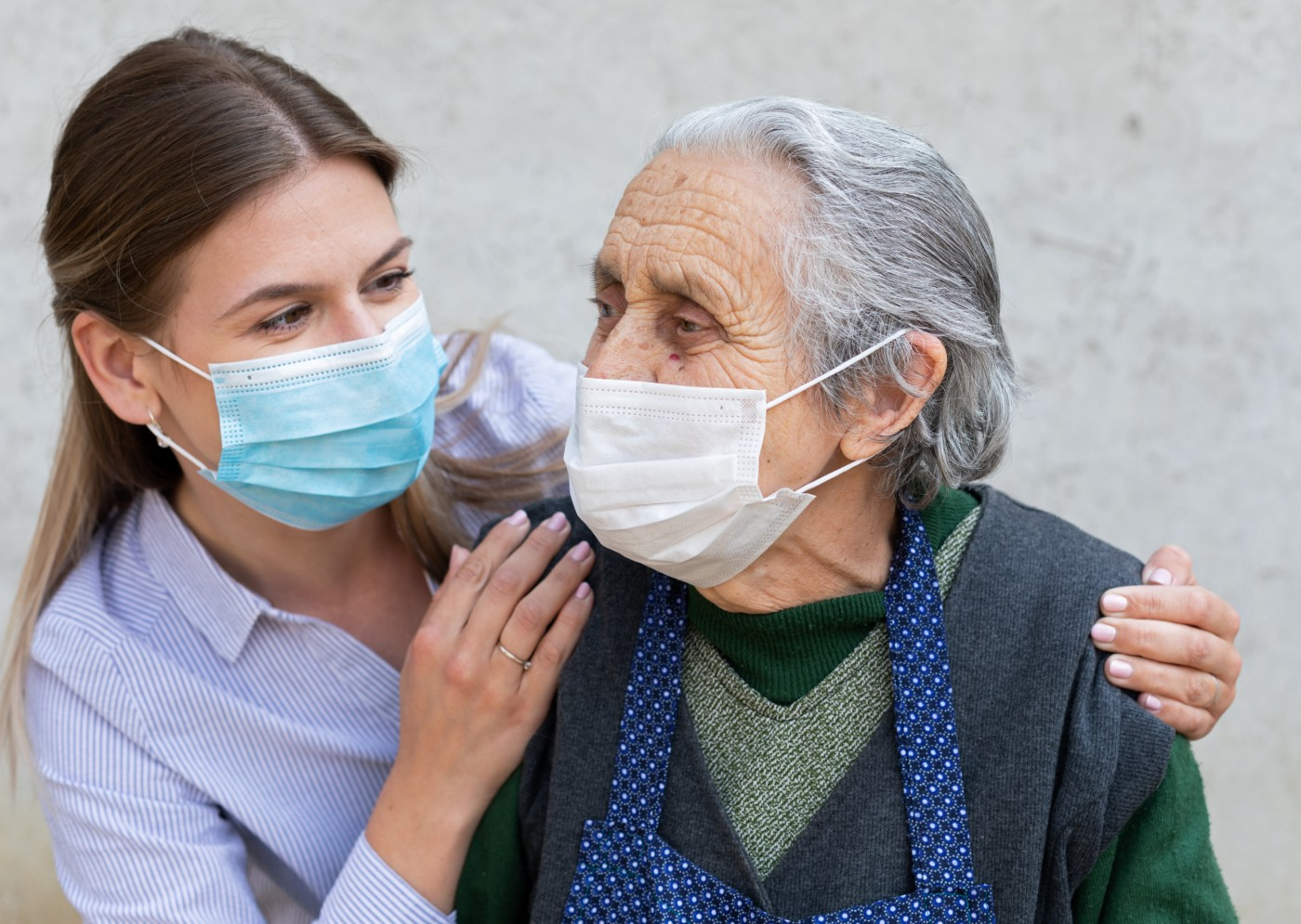 elderly and younger women standing side by side looking at each other