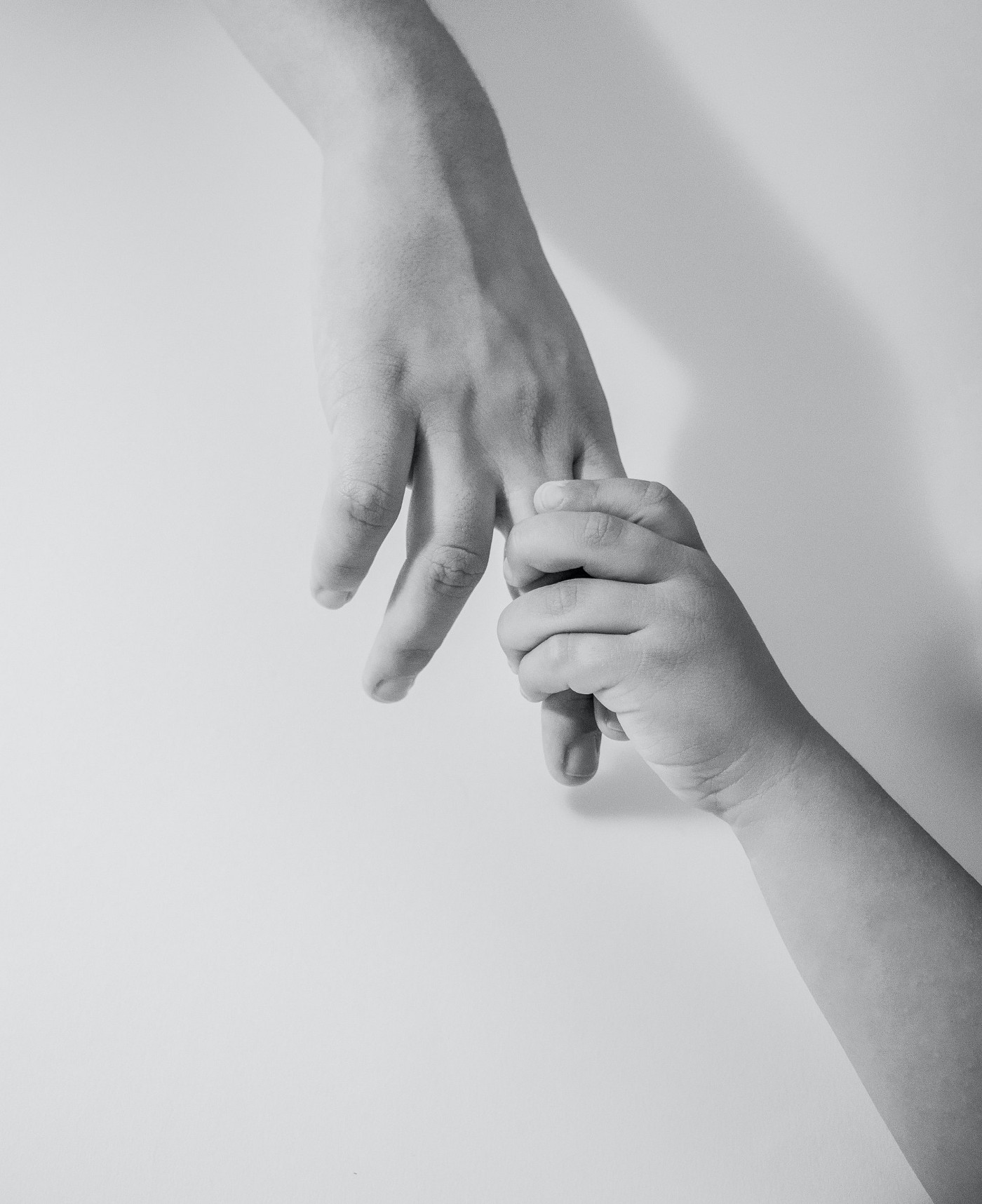 A child' hand holding the hand of an adult