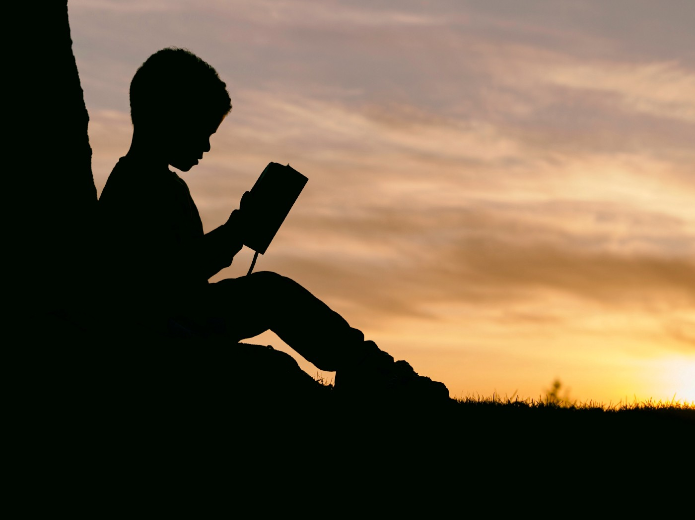 A kid, sitting in a twilight and staring into an open book