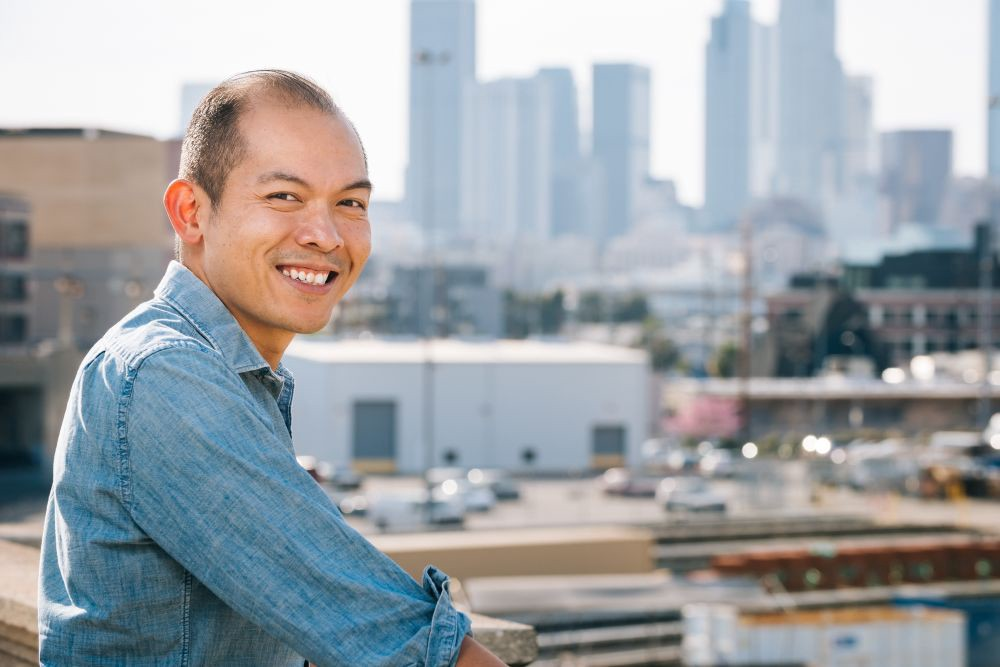 A Filipino man—Godfrey—smiling against the backdrop of Downtown Los Angeles.