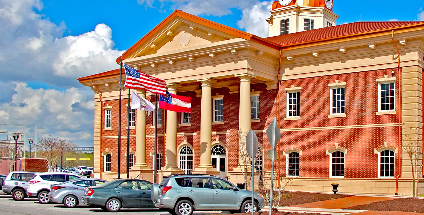 City hall building with cars parked outside and three flags flying out front: the US flag, the state flag of Georgia, and the city flag of Sugar Hill