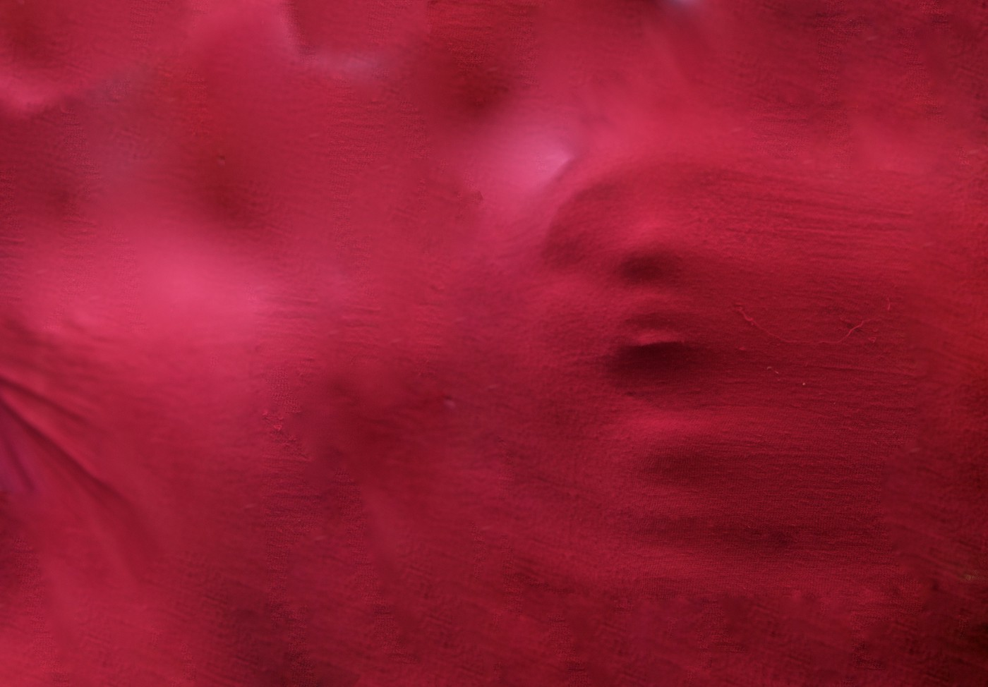 A screaming face coming through red fabric.