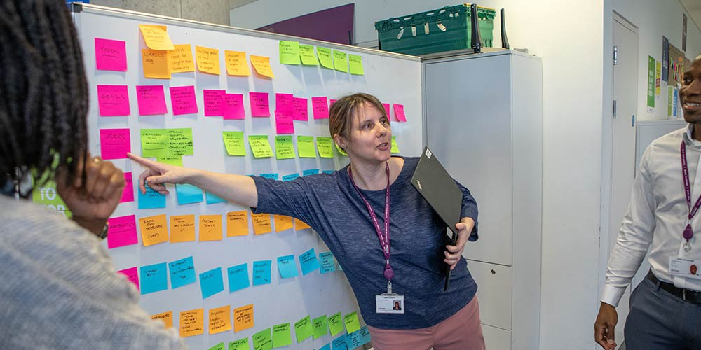 """Annie Heath in a classic """"point at post-it"""" pose"""