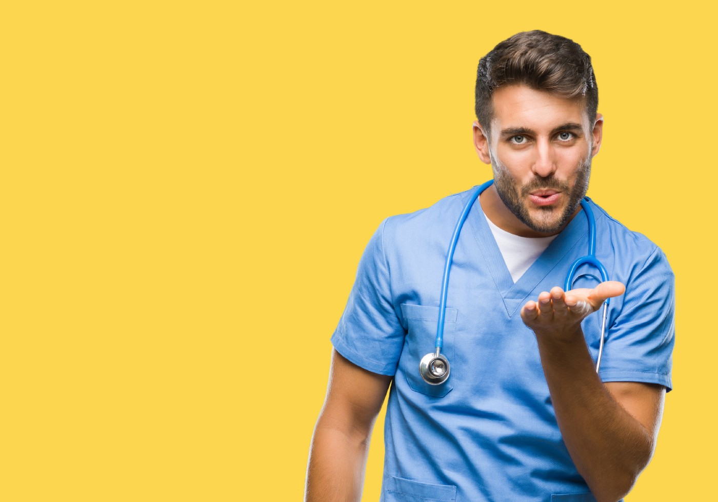 Young handsome doctor surgeon man over isolated background looking at the camera blowing a kiss with hand on air being lovely and sexy.