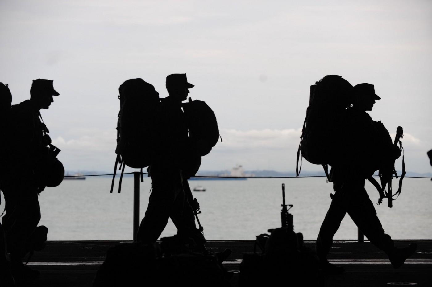 Three army soldiers lining up as they embark on a mission at sea in full combat gear, looking like black shadows against the grayish sky.