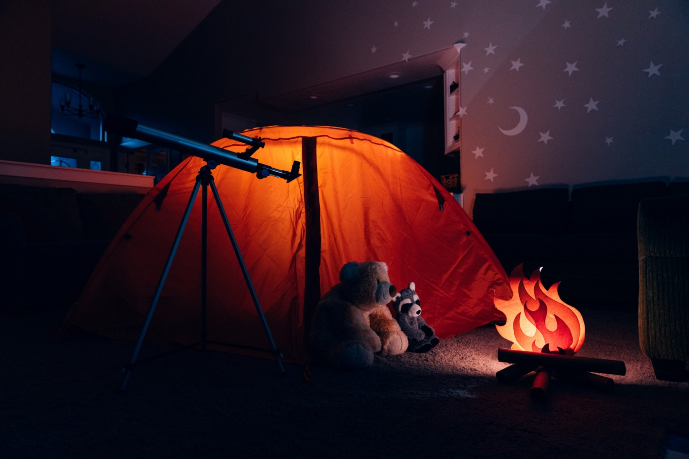Tent and fake campfire set up indoors with stuffed animals huddled around the fire and a telescope.