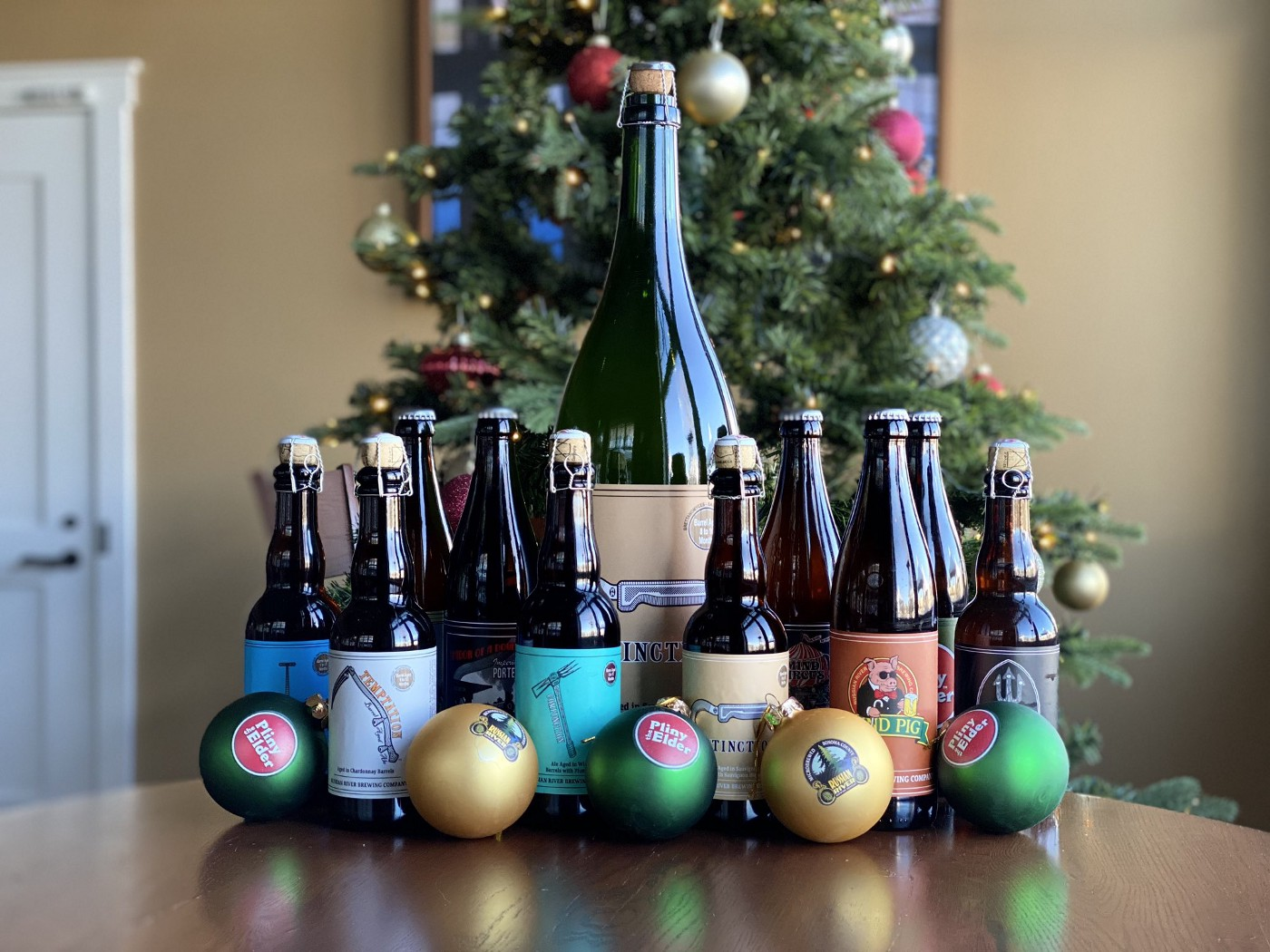 An assortment of small bottles of beer around a large one, all in front of a Christmas tree.