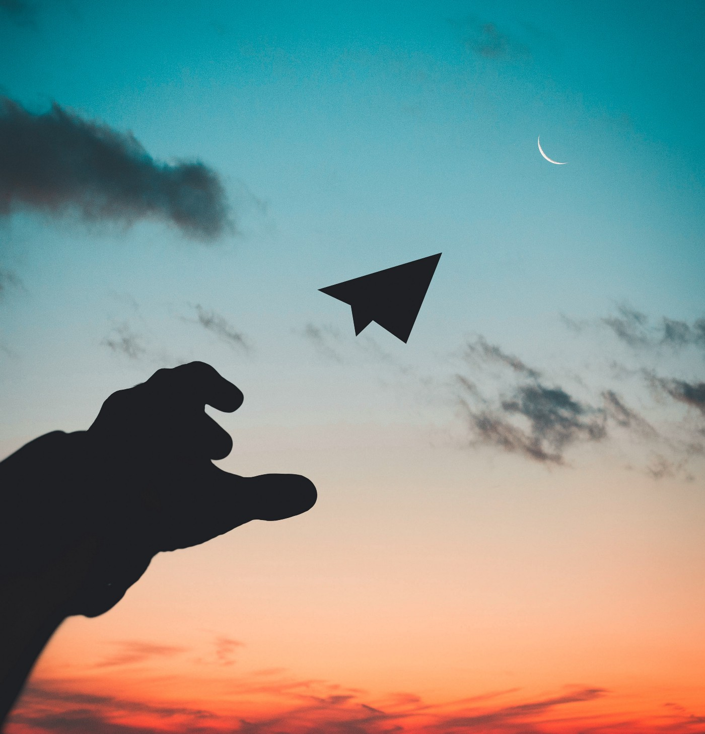 A silhouted hand tosses a paper airplane at the moon during sunset.