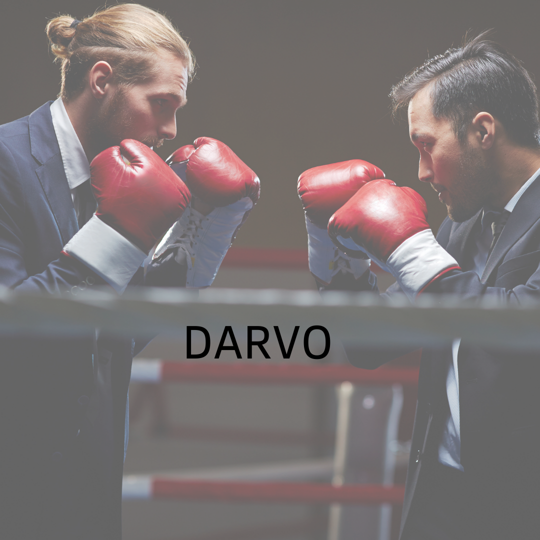 two men in suits face each other in a boxing ring wearing boxing gloves. Text in black reads, 'DARVO.'