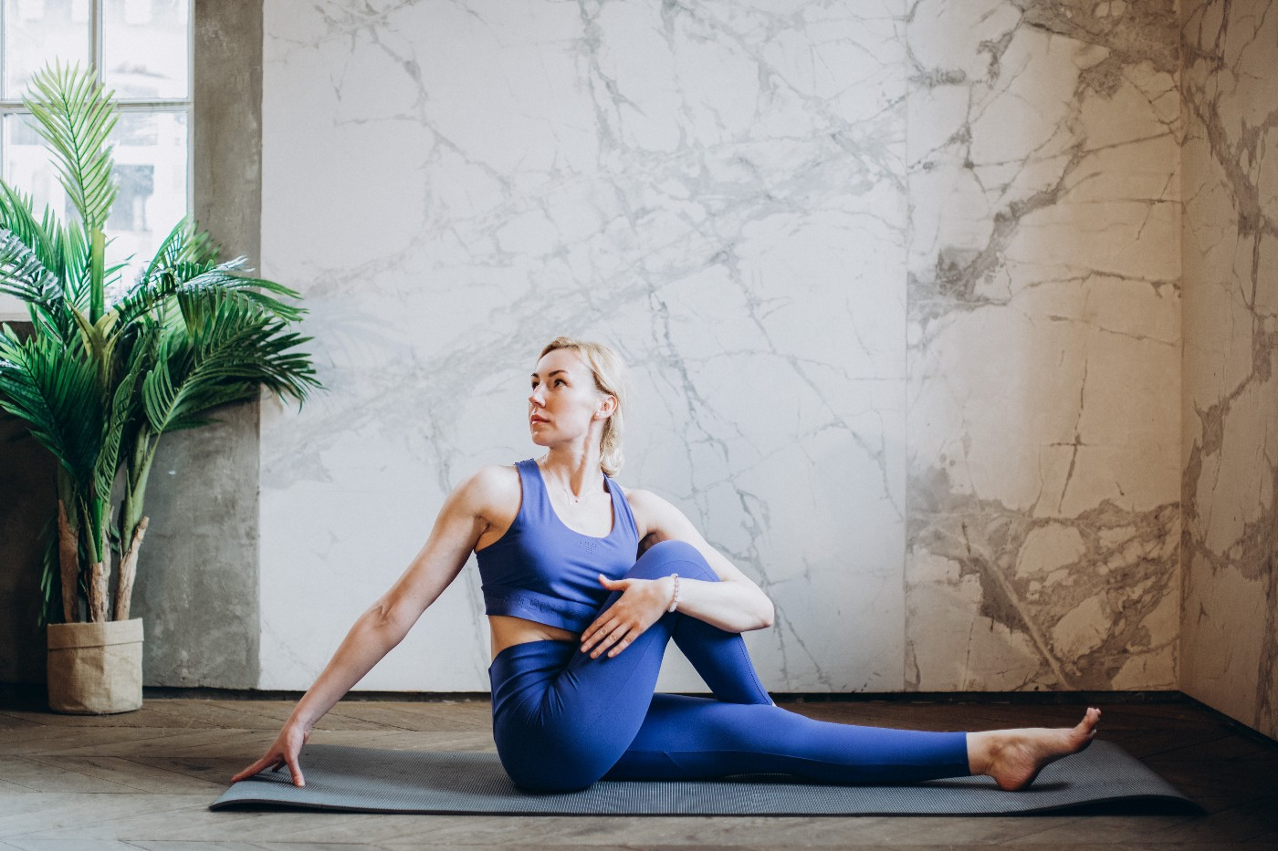 Woman in blue outfit doing yoga on a mat