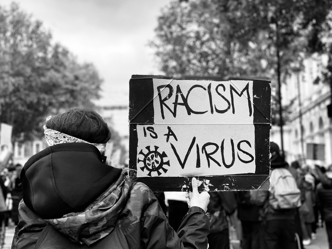 "A Person holds a sign reading ""racism is a virus"". They are wearing a black hoodie and look to be attending a protest."