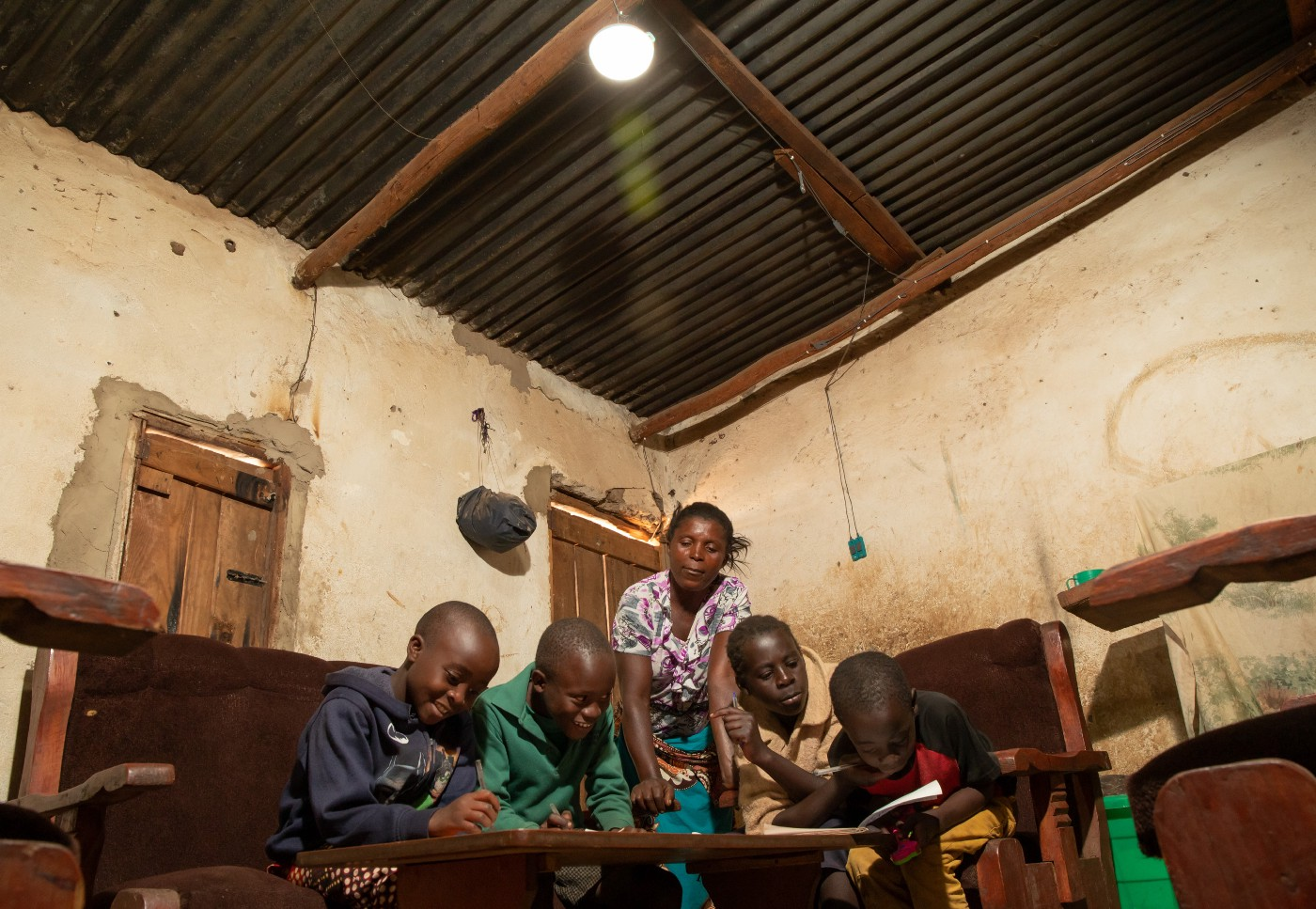 With light from a solar-powered lamp, children are able to do homework at night.
