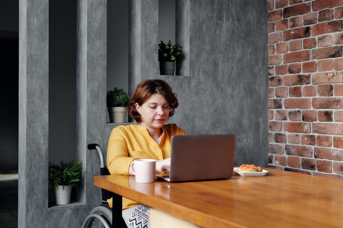 A woman sitting at her kitchen table, eating breakfast while working on her laptop