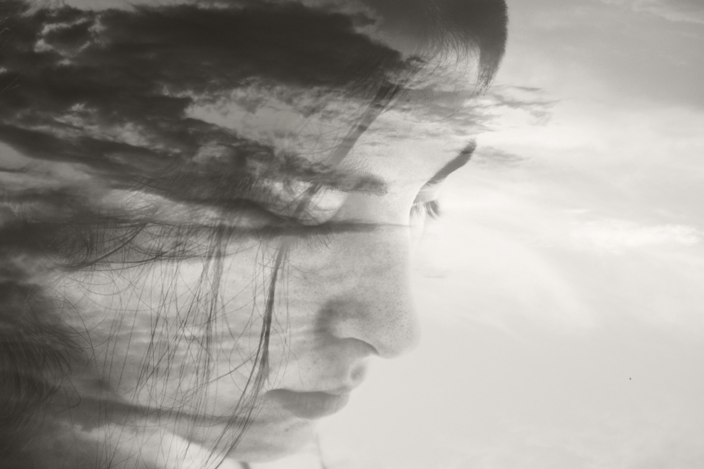 A black and white superimposed photo of a cloudy sky and a woman's face.