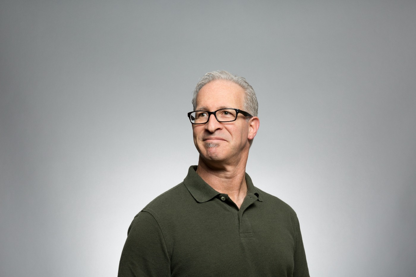 A head and shoulders shot of a white man with greying hair and glasses standing tall and looking somewhat proud of himself.