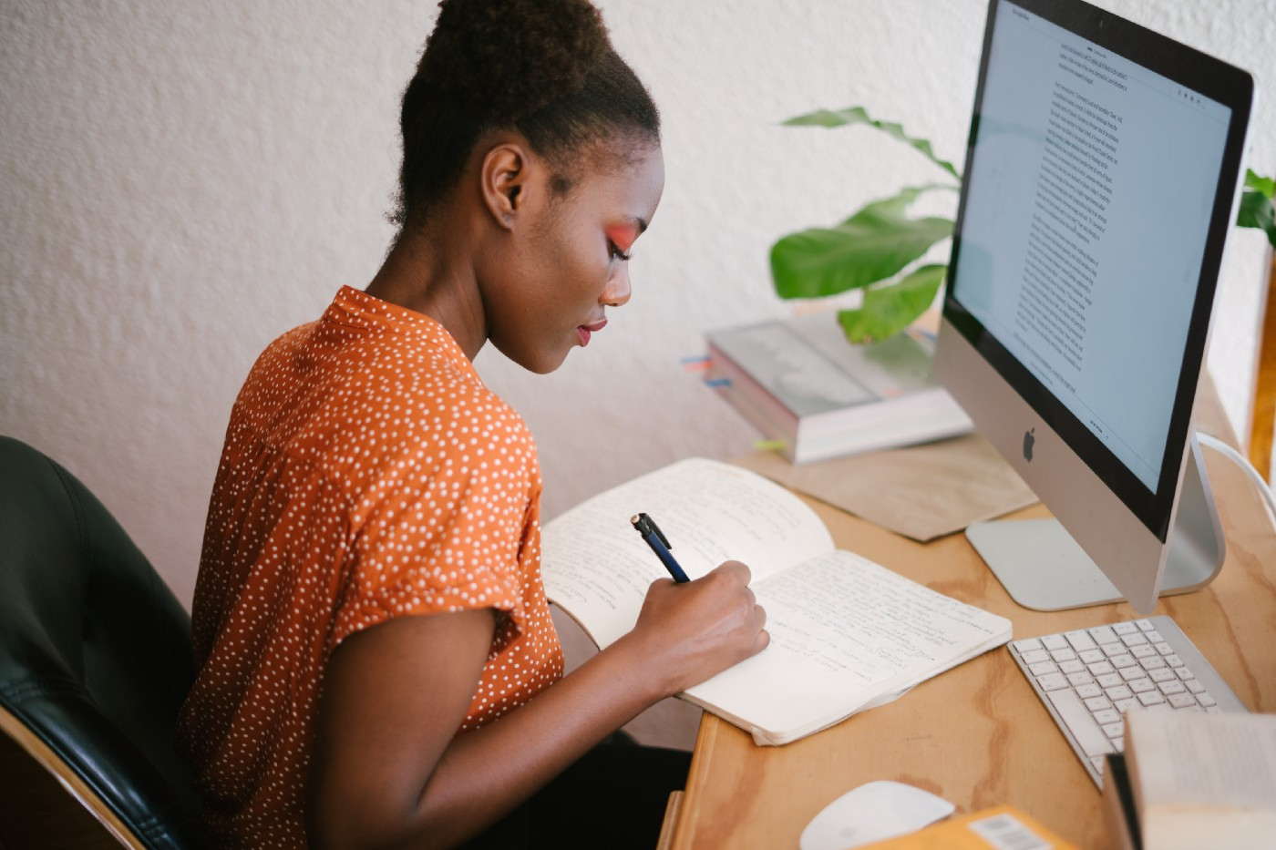 An African girl sitting down and writing into her notepad in front of a Mac computer screen