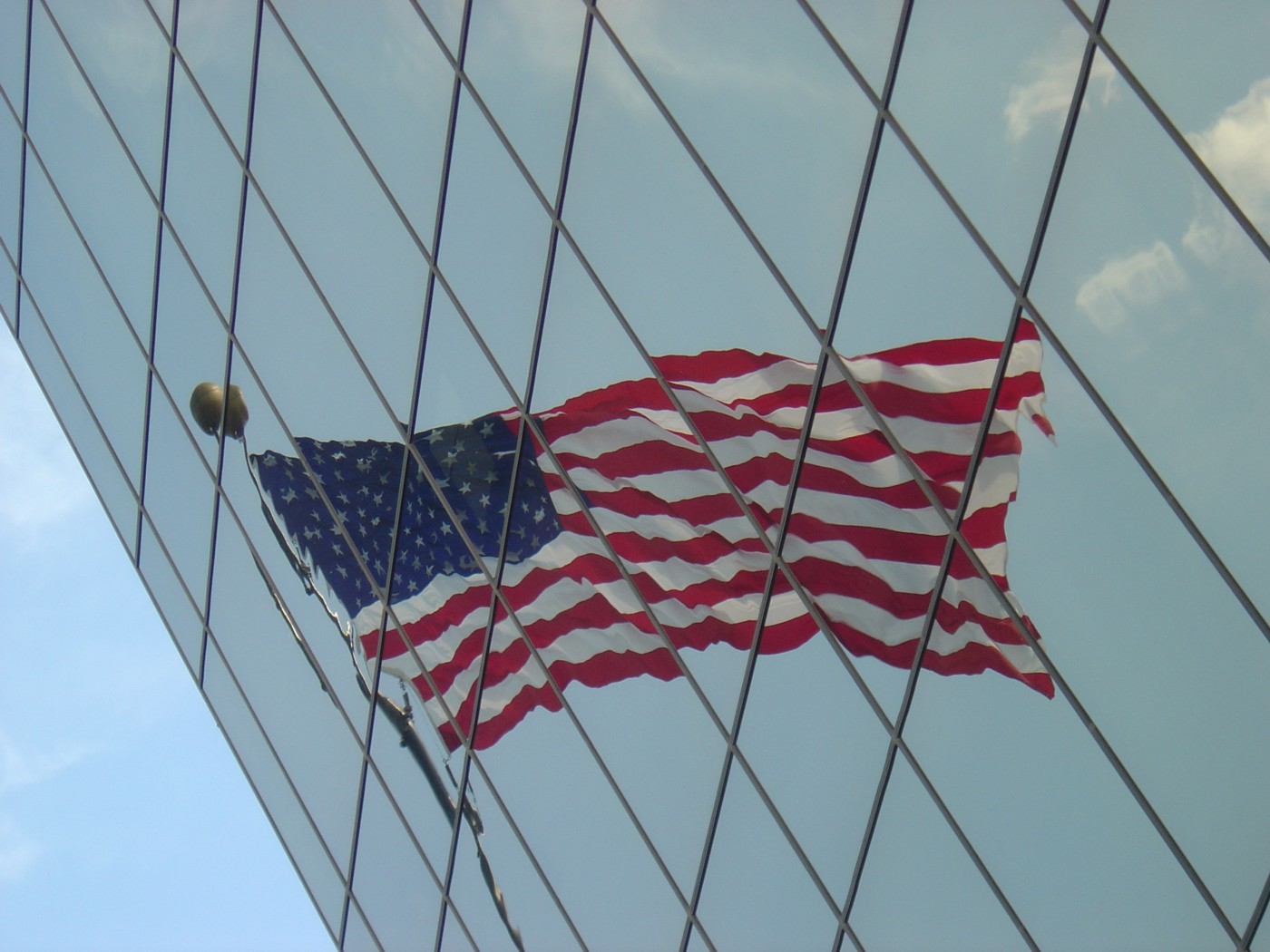 American flag reflected on the glass surface of a building, distorted.