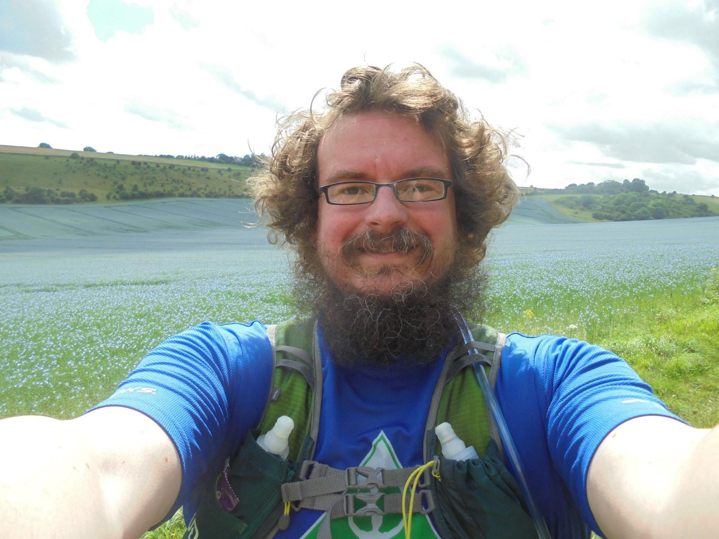 head shot of a bearded human in running kit looking into the camera with a field of cornflowers in the background