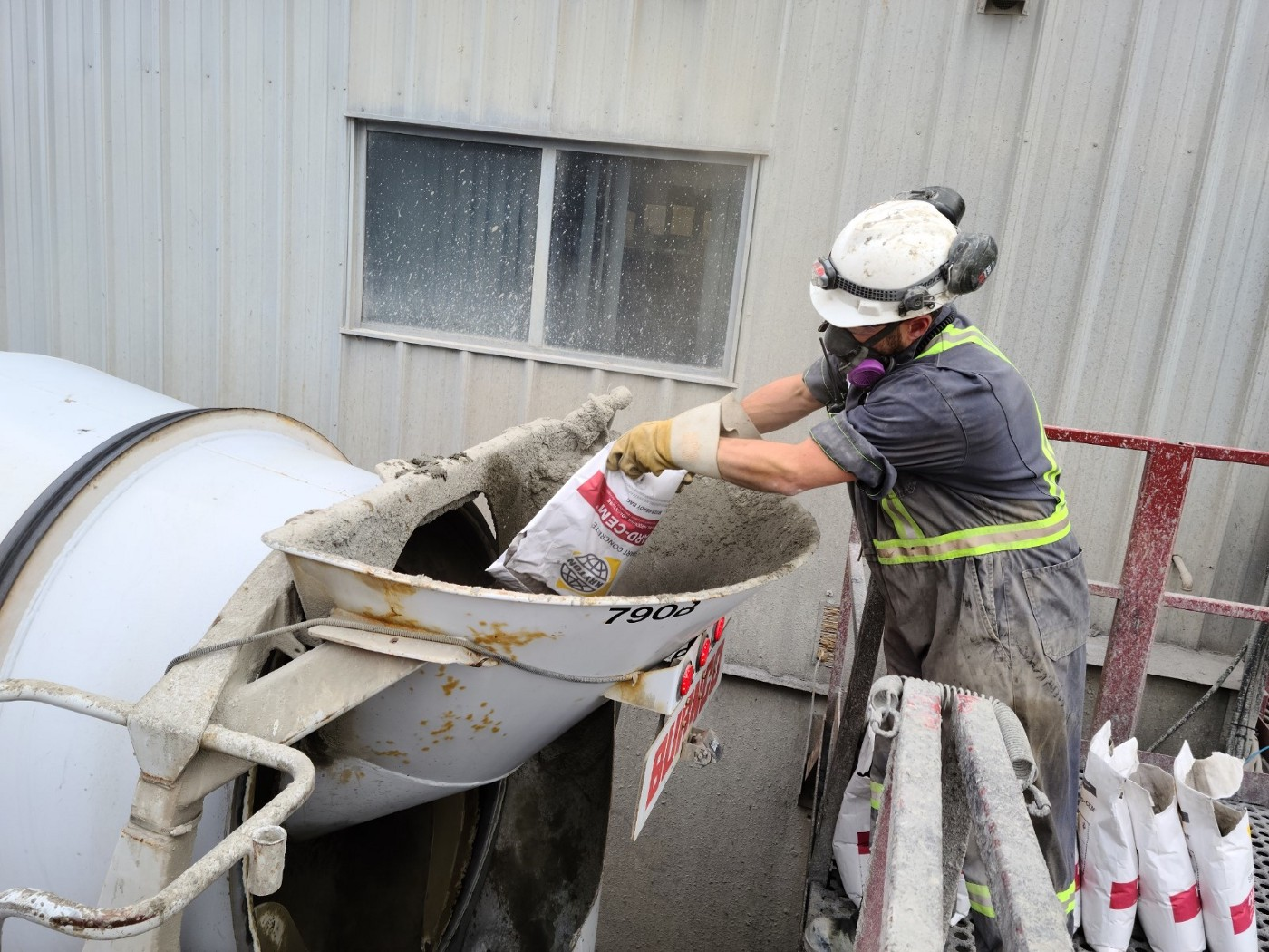 A construction worker is adding Hard-Cem into his concrete mix during batching.