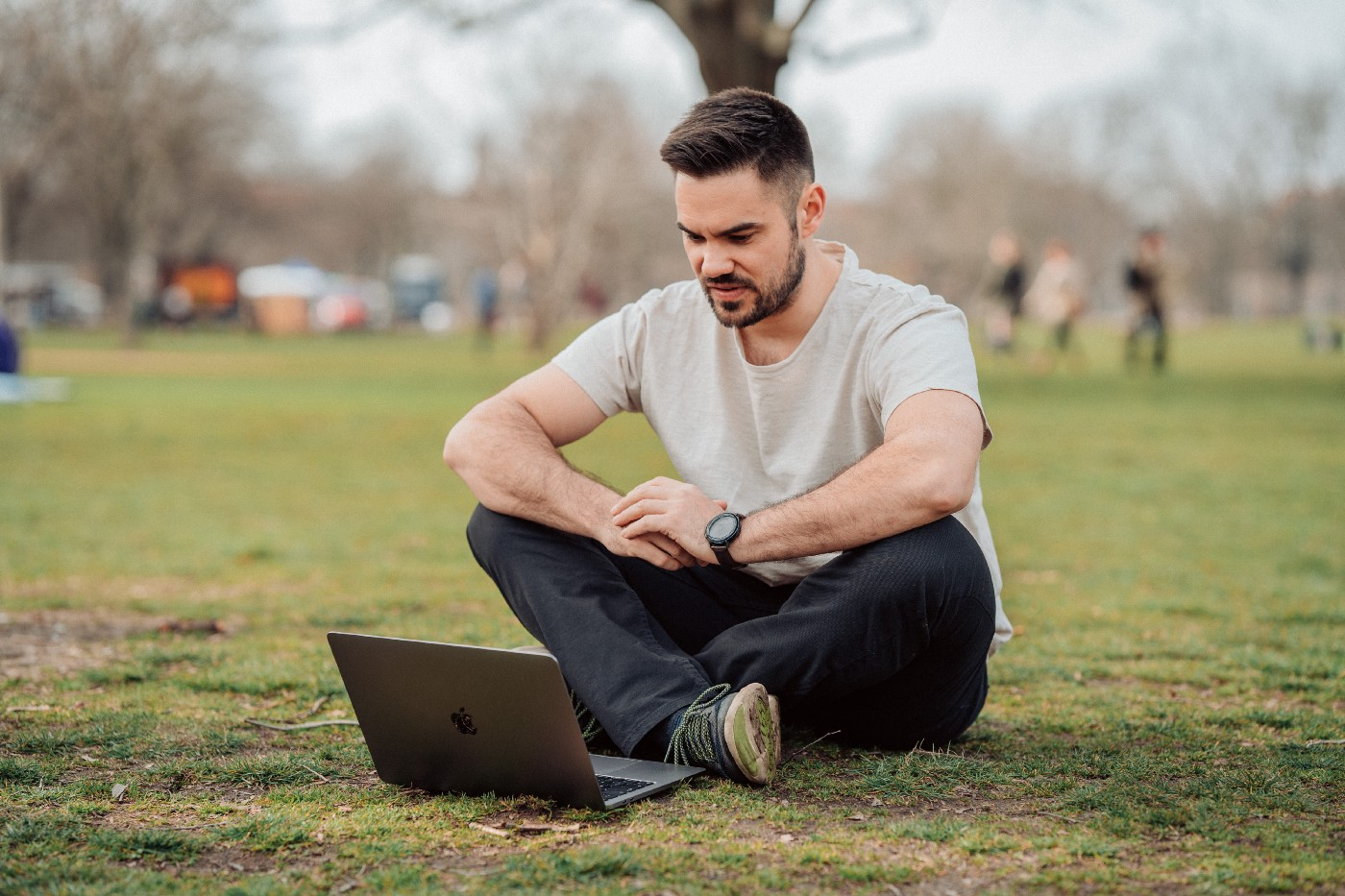 A man sitting behind his MacBook on the ground on a park