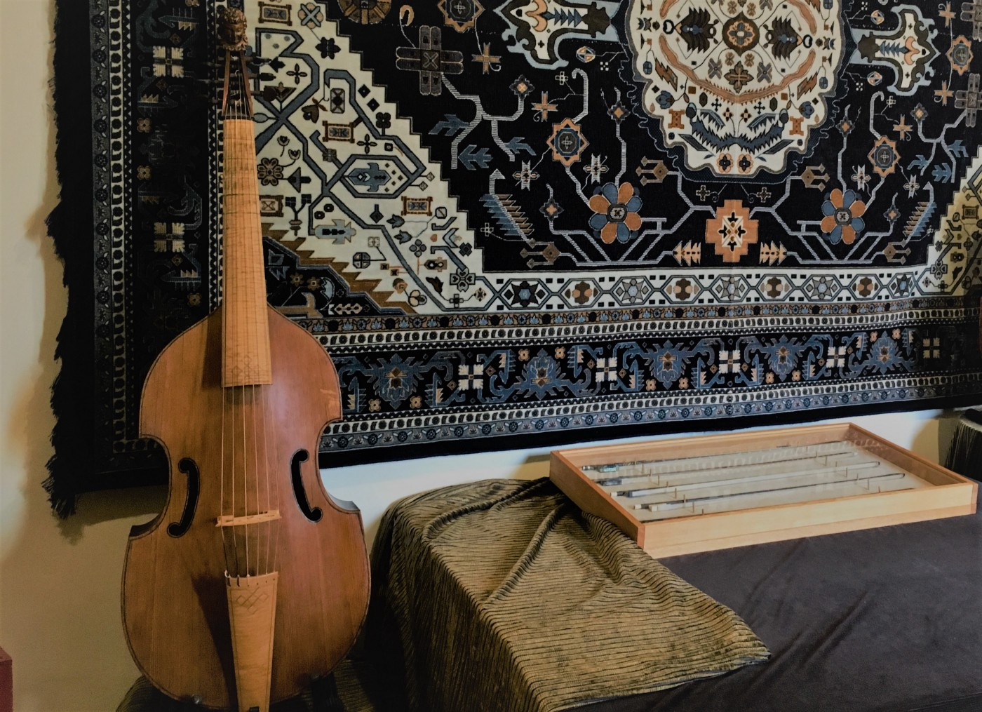 A photo of a viola da gamba, a cello-like instrument from the 15th and 16th centuries. In the background is a carpet-like tapestry and the table beside the instrument has a box with bows for the instrument.