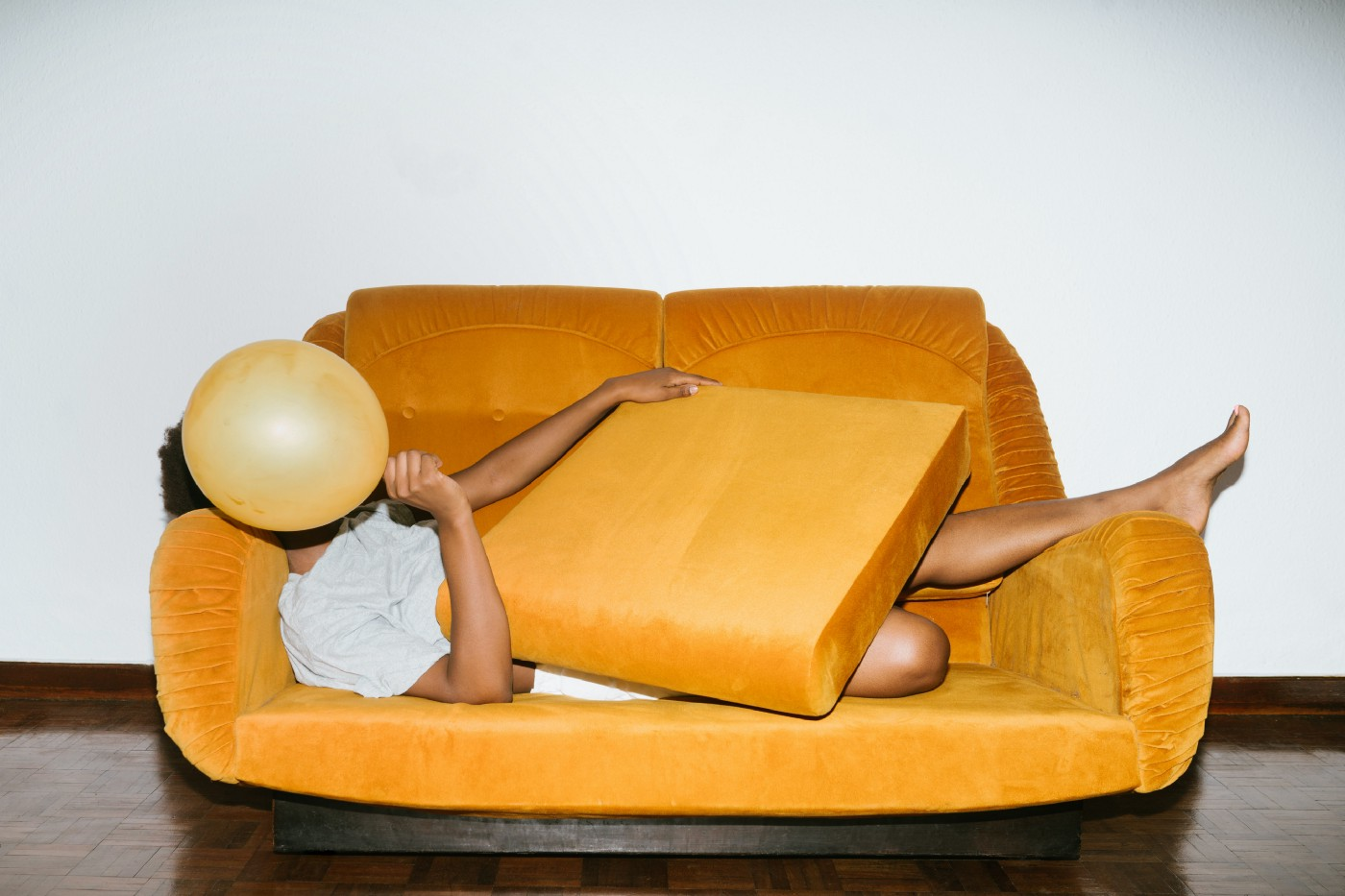 human is hiding behind a pillow and a ballon