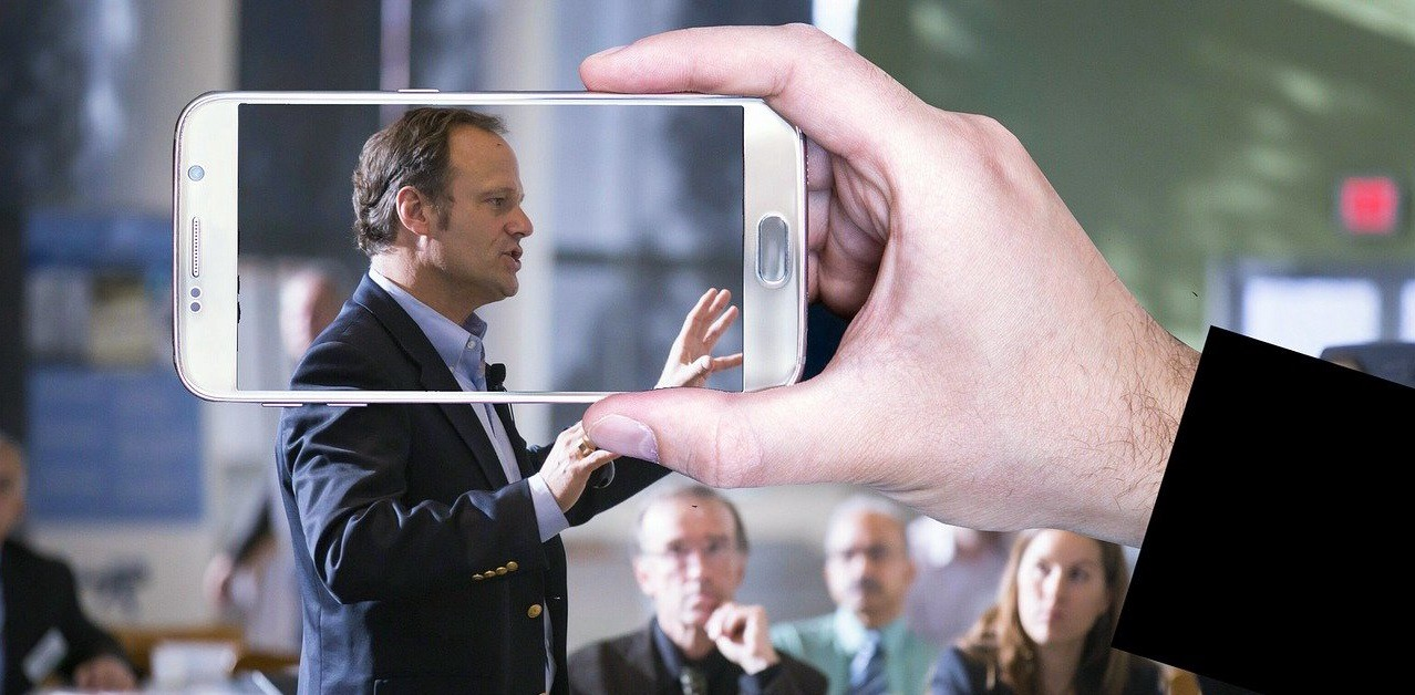 Man speaking in public while someone snaps his picture with a smartphone