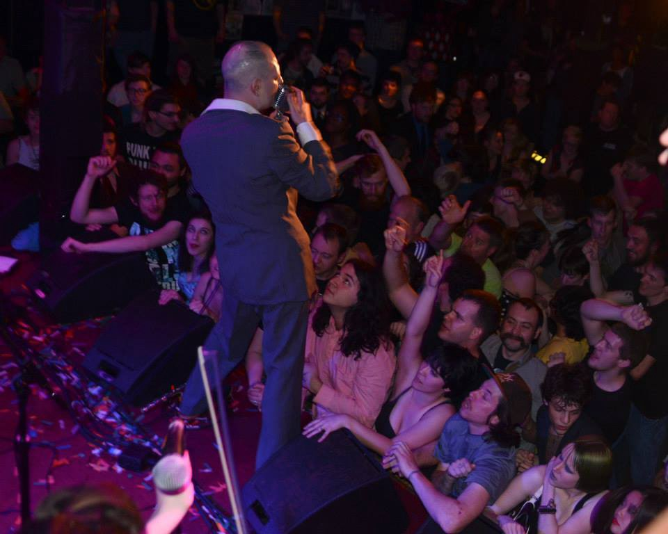 Jack Terricloth, lead singer of punk band The World/Inferno Friendship Society, shown from the perspective of the band as he sings onstage at a bar. An enthusiastic audience faces him, gesturing and dancing as they sing along.