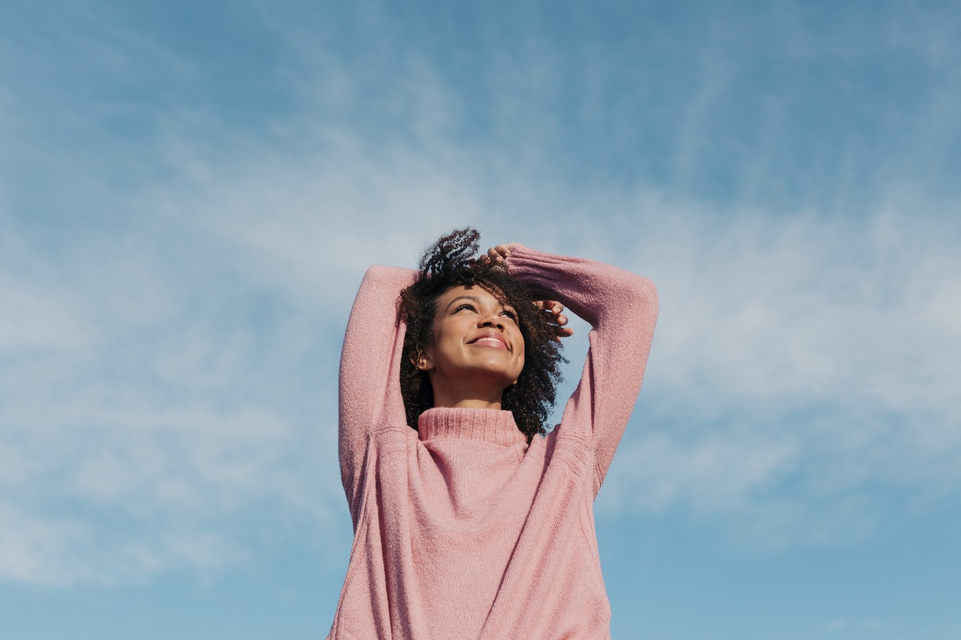 A portrait of a happy young woman enjoying the sunlight with the sky as a backdrop.