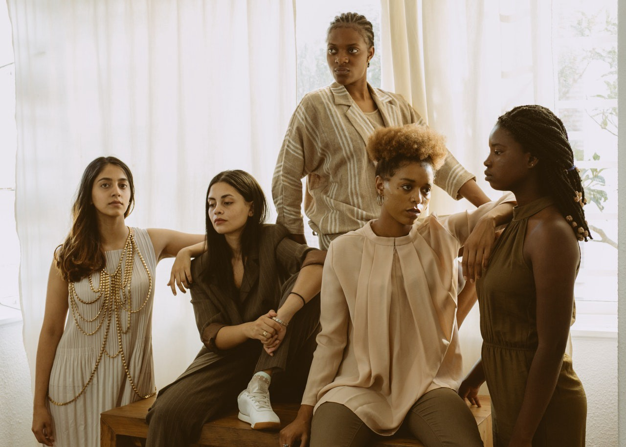 5 different women sitting and standing all together at a photo shooting