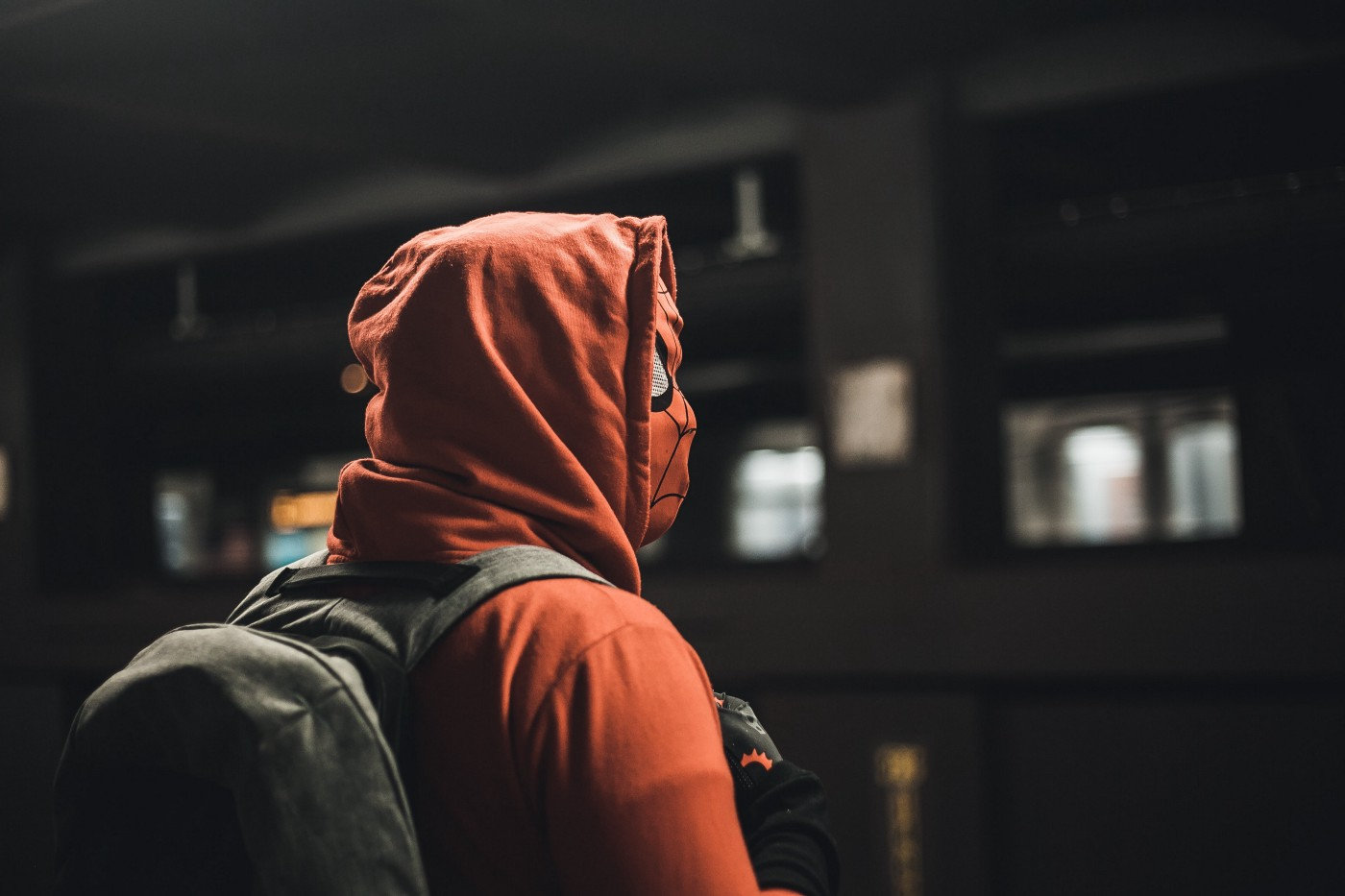 A person in a red hoodie. The hood is pulled up, they wear a grey backpack, and their face is concealed behind a Spider-Man mask. They appear to be waiting for the subway.