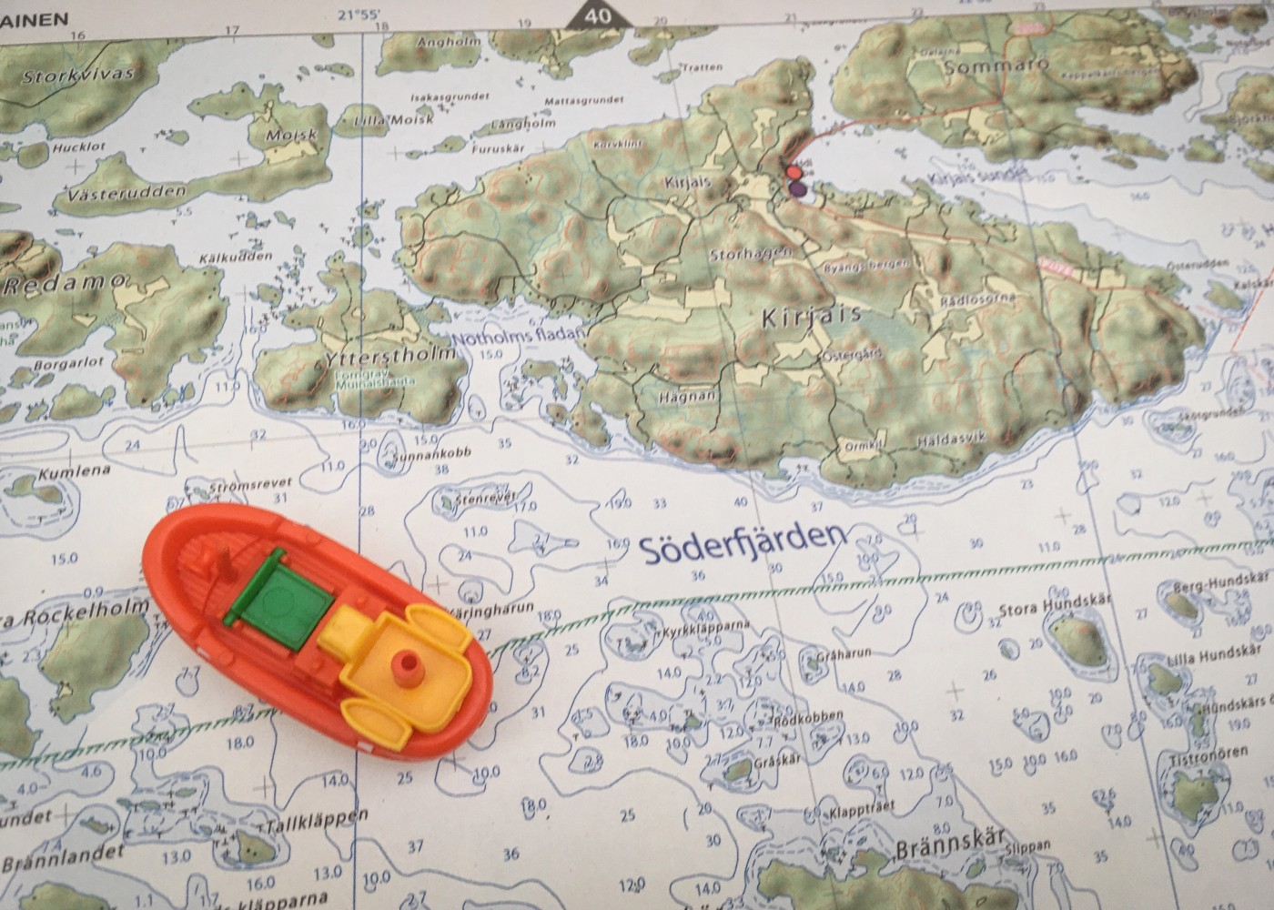 A toy boat sits on the page of a nautical atlas.