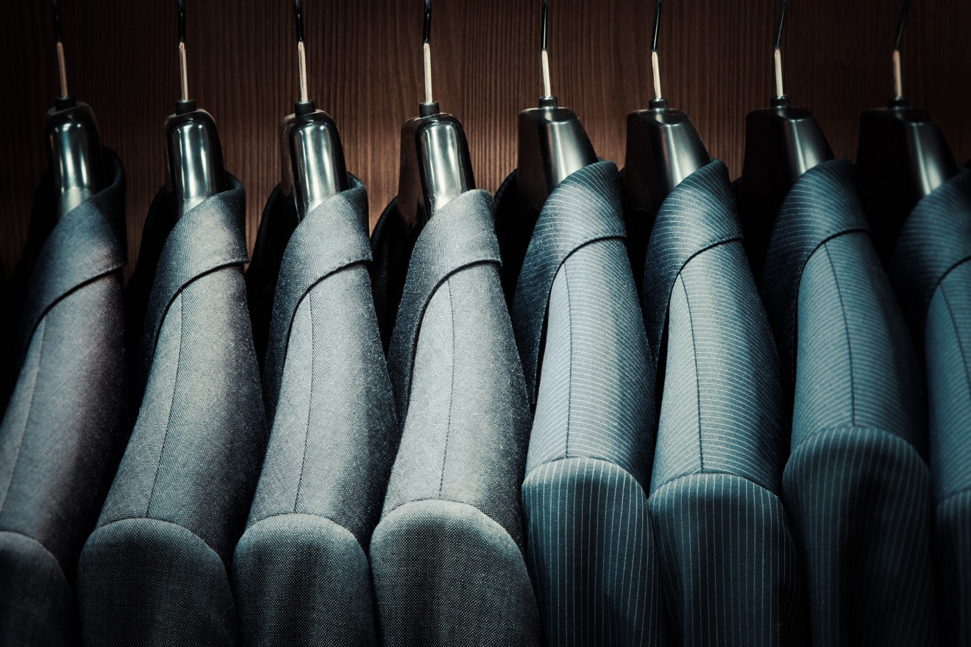 Dark wall with a rack of suit blazers in various shades of gray