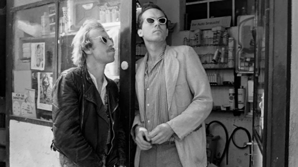 Two men with matching sunglasses stand in the doorway of a bodega.