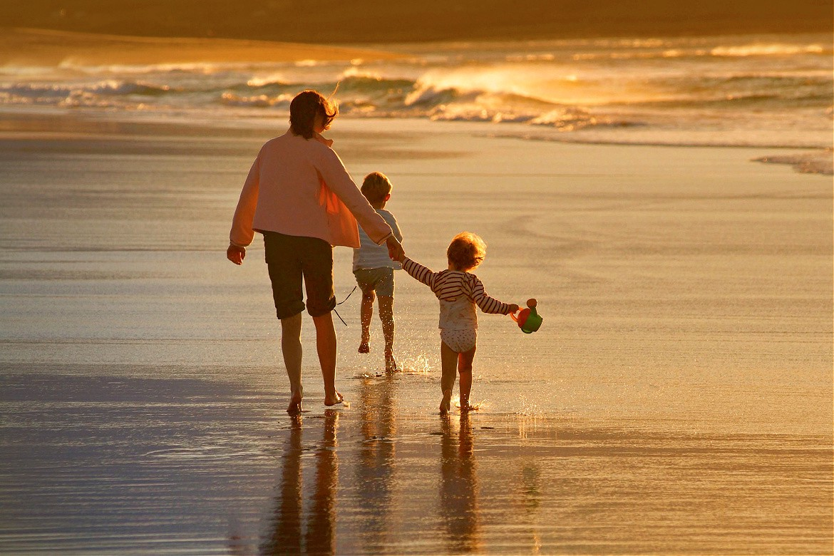 Woman and two children walking on the beach at sunset