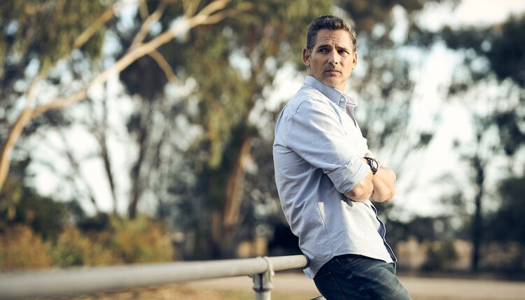 Eric Bana leans against a railing in a still from movie The Dry (2021).