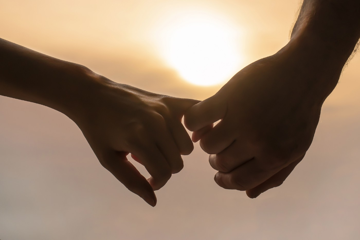 A close up of male and female hands linking their little fingers, in front of of a sunrise.