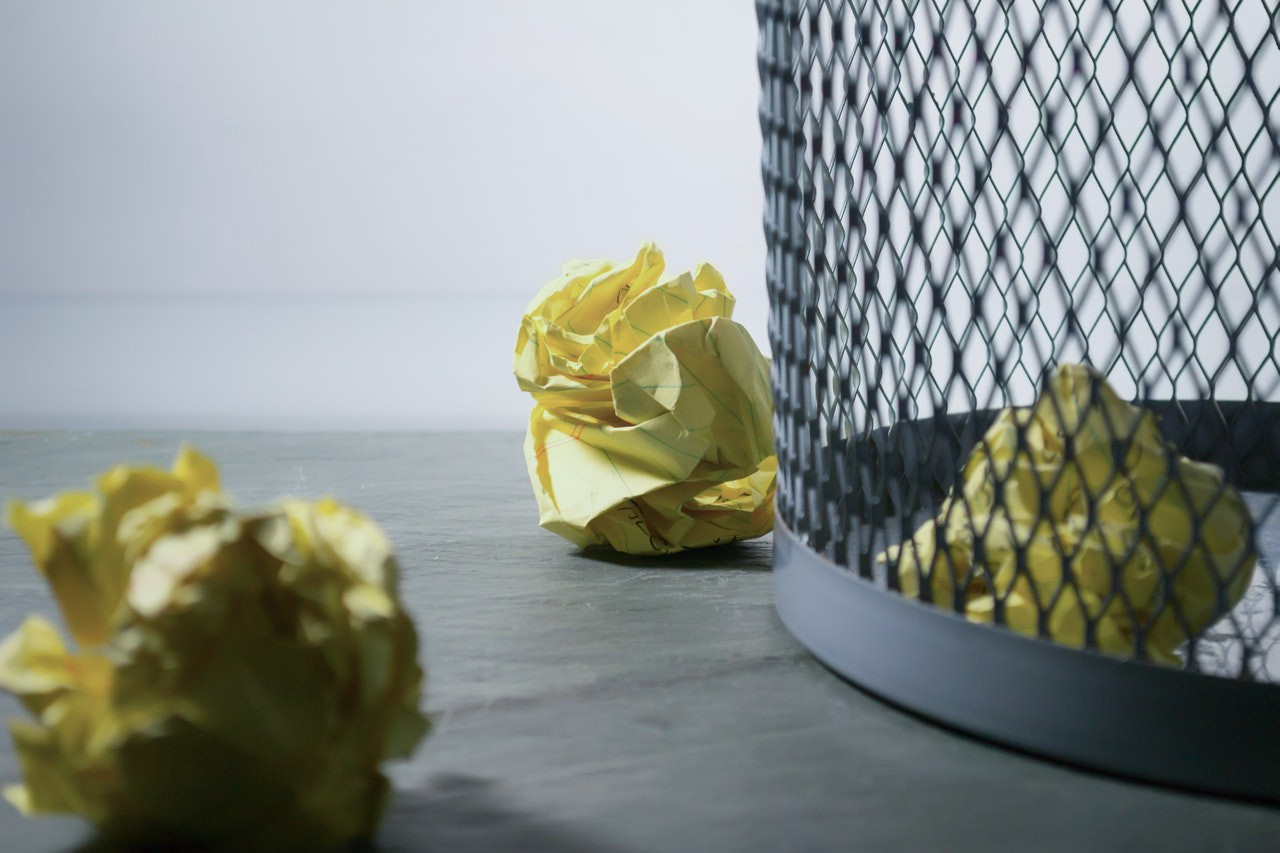 Yellow paper crumpled into balls near a wire wastebasket.
