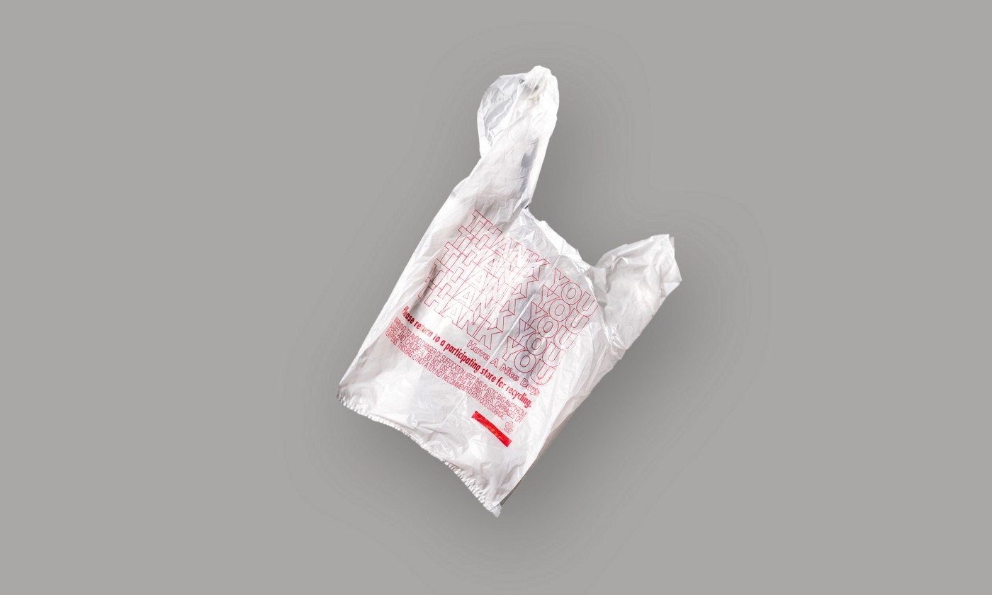 """White plastic grocery bag with red """"thank you"""" text on gray background"""