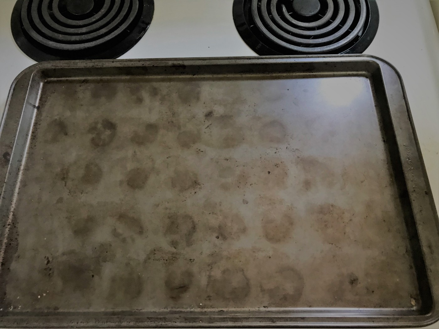 Old baking sheet with 40 dark circles etched into the surface (5 x 8)